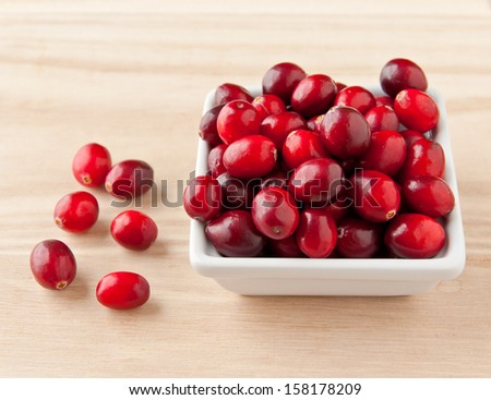Cranberries in bowl on wooden board, healthy vitamin food. selective focus - stock photo