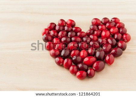 Cranberries in heart shape on wooden board, healthy vitamin food. selective focus