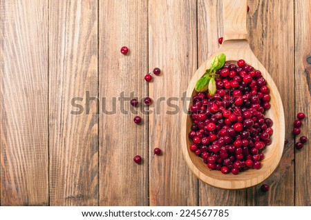 cranberries in wooden spoon on table - stock photo