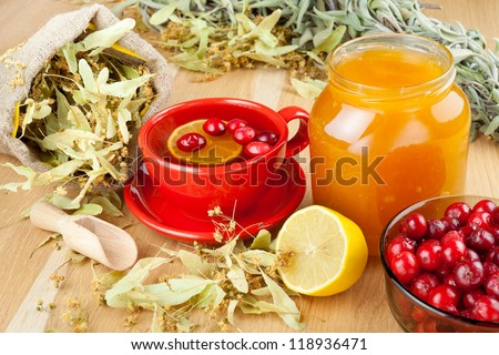 cranberries, jar with honey, fruit tea cup, healing herbs and lemon - stock photo