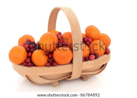 Cranberry and mandarin christmas fruit arrangement in a rustic wooden basket isolated over white background. - stock photo