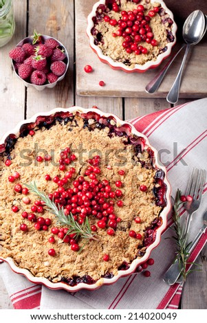 Cranberry, bilberry crumble with rosemary on a wooden and textile background - stock photo