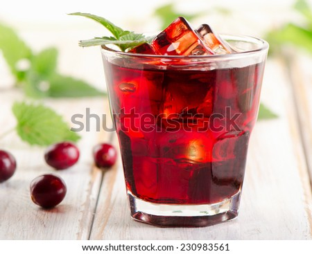 cranberry cocktail with mint on a white wooden table. Selective focus - stock photo