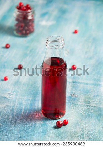 Cranberry fruit drink in bottle on a blue background. Selective focus - stock photo