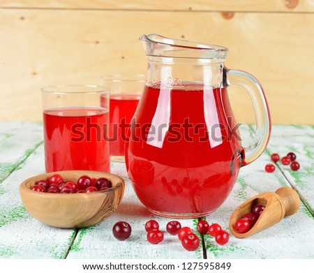 Cranberry juice in a jug on a white table - stock photo