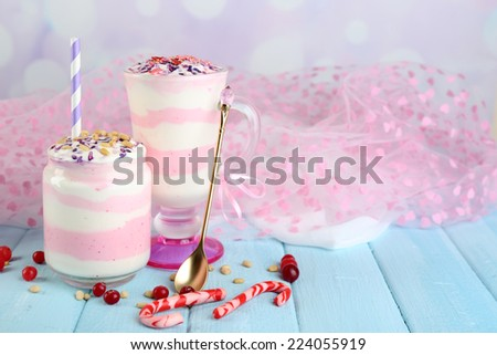 Cranberry milk dessert in glass and glass jar, on color wooden table, on light background - stock photo