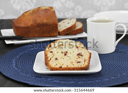 Cranberry pound cake, slices on a plate and whole one in background with a mug of hot coffee. - stock photo