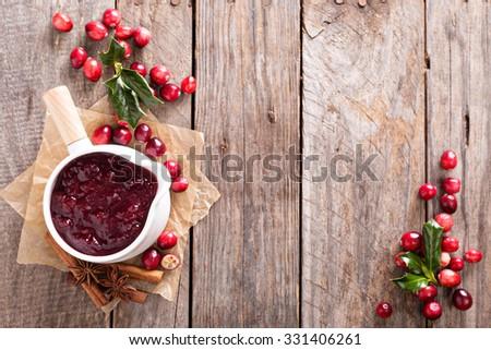 Cranberry sauce in ceramic saucepan on dark background - stock photo