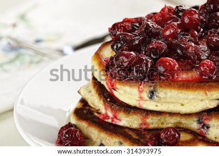 Cranberry sauce made with maple syrup, butter and fresh cranberries over delicious golden pancakes for Christmas morning. Extreme shallow depth of field with selective on pancakes. - stock photo