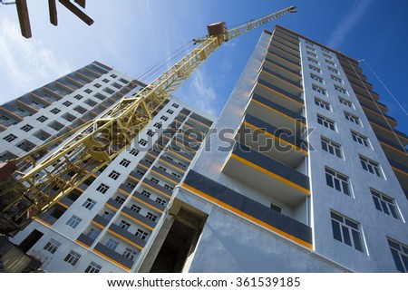 crane against sky building a new block of flats. new multi-storey house. Building crane and building under construction against cloudy sky. - stock photo