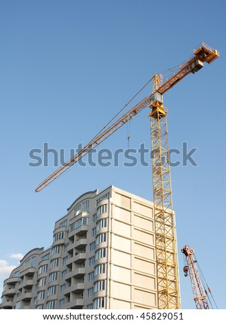 Crane and a building construction - stock photo