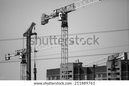 Crane and building construction construction site black and white photography - stock photo