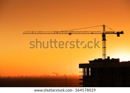 Crane and building silhouette on red sunset sky background