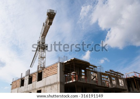 Crane and construction site with bright blue sky