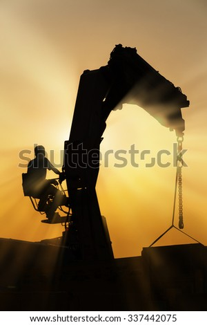 Crane and worker in Construction site under sunset  - stock photo