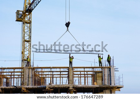Crane and workers at construction site. - stock photo
