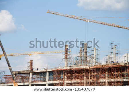 Crane and workers at construction site against blue sky. Thailan