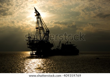 Crane barge and oil rig in the sunset