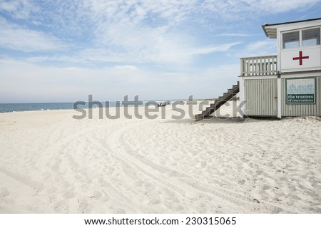 CRANE BEACH, MASSACHUSETTS, USA -SEPTEMBER 30, White sand and lifesaver station with red cross  and insignificant people sunbathing on September 30, 2014 at Crane beach, Massachusetts, USA,  - stock photo