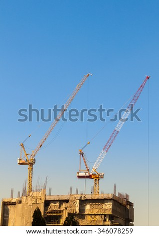 Crane constructing sky scrapper in Thailand, morning sky with gradient light