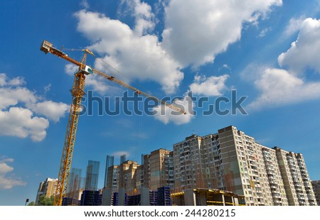 Crane constructing the building in the city - stock photo