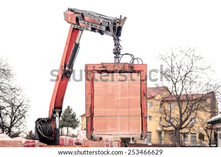 Crane delivers a brick pallet at building construction site, isolated on white sky  - stock photo