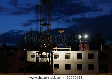 Crane downs slab, workers on building under construction at night - stock photo