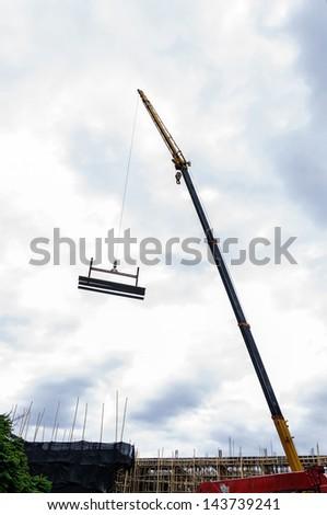 Crane hoist concrete plate at construction site - stock photo