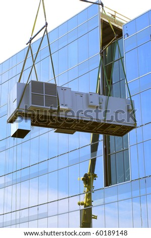 crane hoisting cooling system to the top of a glass building - stock photo