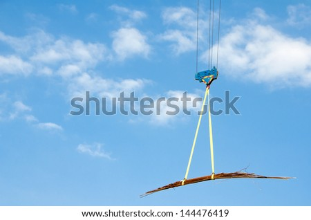 Crane hook lifting steel on a cloudy sky