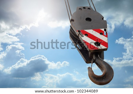 Crane hook on a blue sky - stock photo