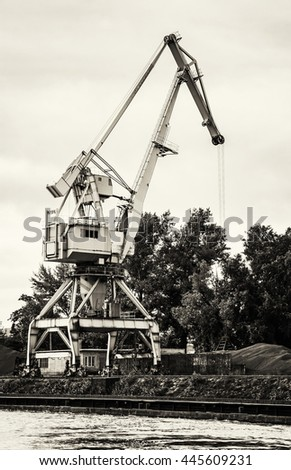 Crane in cargo port translating coal. Industrial scene. Black and white photo. Big port-crane. Vertical composition. - stock photo