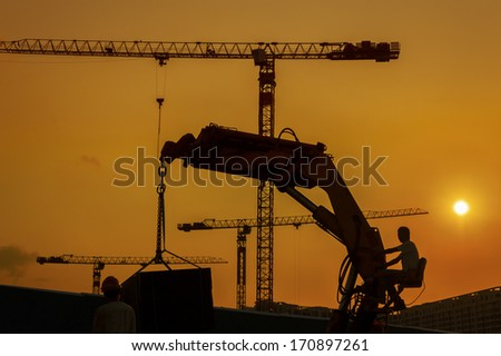 Crane in construction site under sunset  - stock photo