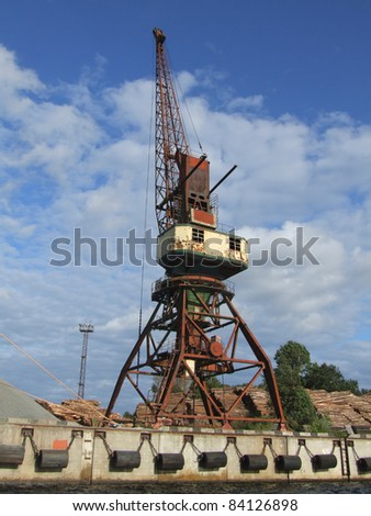 Crane in Riga port with logs nearby