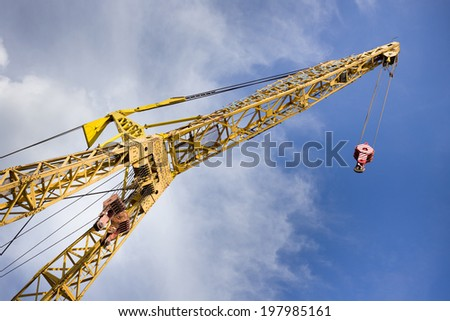Crane in the river harbor with dynamic clouds and blue sky in background - stock photo