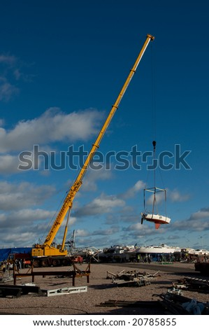 Crane lifting a sailing boat