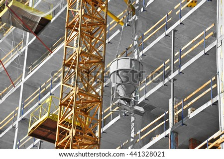 Crane lifting concrete mixer container on construction site