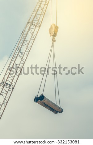 Crane lifting pipes. Crane hook with two pipes. Vintage style. - stock photo