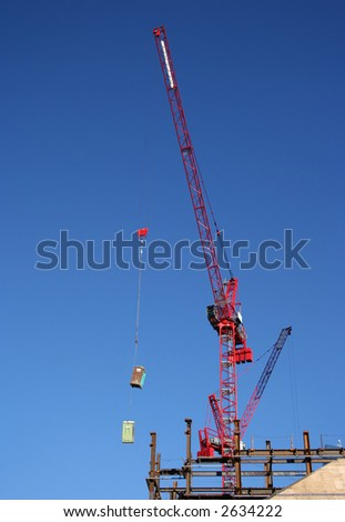 Crane lifting portable toilets at building site - stock photo