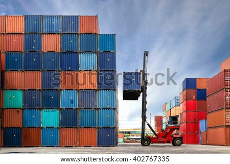 Crane lifting up container in yard - stock photo