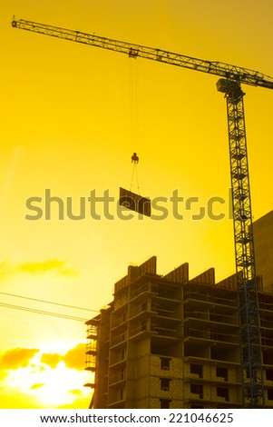 crane lifts the concrete plate load on a house under construction in the background of a sunset.vertical shot against sunset sky background with evening sun Empty copy space for inscription  - stock photo