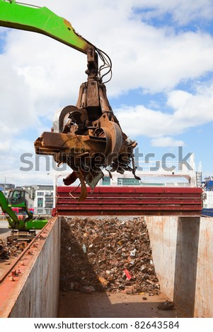 Crane Loading A Ship With Recycling Steel - stock photo