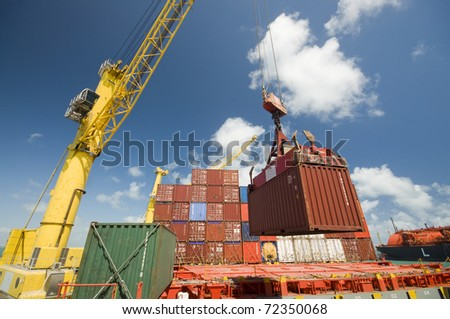 crane lowering container to stack of containers - stock photo