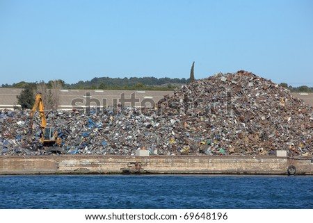 Crane next to a huge pile of metal scrap - stock photo