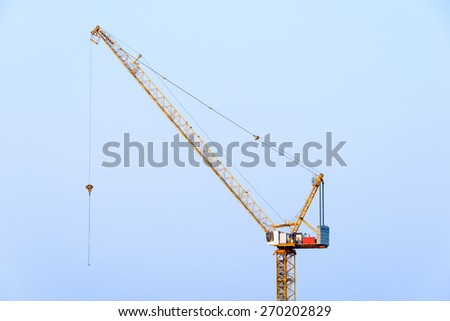 Crane on a top of building - stock photo
