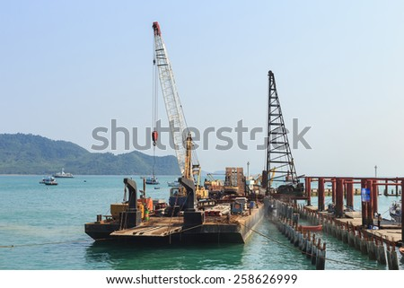 crane on construction site at the pier - stock photo
