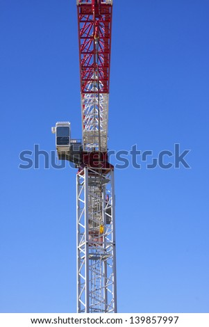 Crane operators cabin against a clear blue sky