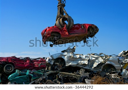 Crane picking up a car in a junkyard - stock photo