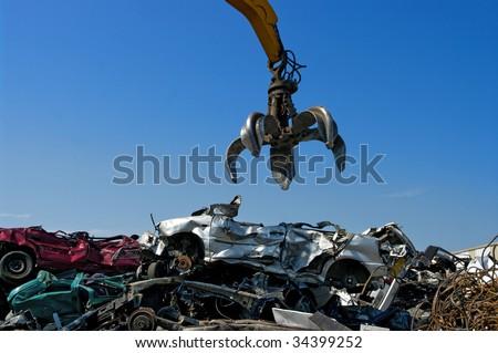 Crane picking up crushed cars - stock photo
