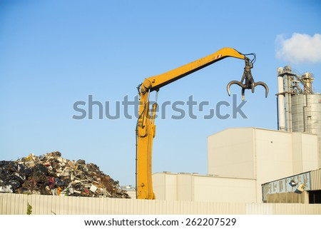 Crane picking up scrap metal in recycling site outdoors - stock photo